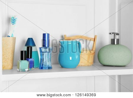 Bathroom set with cosmetics and dispenser on a shelf in light interior