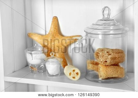 Bathroom set with sponges, starfish and dispenser on a shelf in light interior