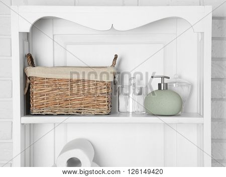Bathroom set with dispenser and sponges on a shelf in light interior