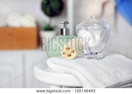 Bathroom set with towels, dispenser and sponges on stool in light interior