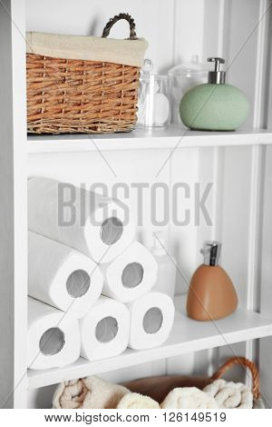 Bathroom set with paper towels, basket and dispensers on a shelf in light interior