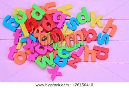 Group of colorful letters on purple wooden table