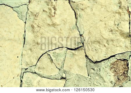 Closeup of old rough broken stone with deep crannies - stone textured background in sepia tones