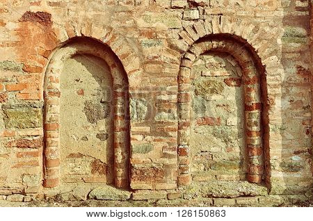 Architectural elements of old church wall known as dead windows. Old wall is made of plinfa - thin calcined brick used in Vyzantium construction.
