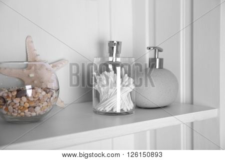 Bathroom set with starfish, dispenser and sponges on a light shelf