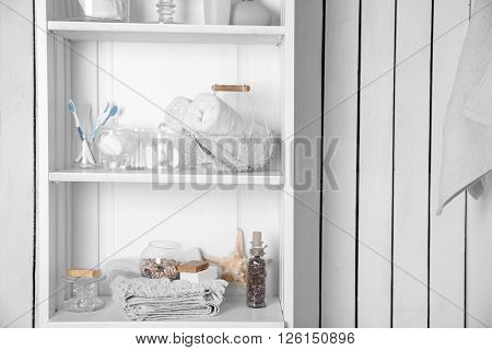 Bathroom set with towels, toothbrushes, sponges and starfish on a light shelf