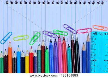 Many school objects on notebook background closeup