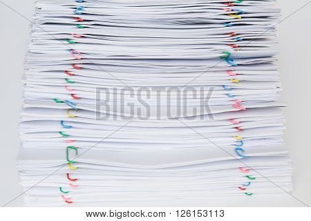 Colorful Paper Clip With Pile Of Overload Paper And Reports