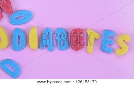 Colorful sugar Diabetes word on pink wooden table