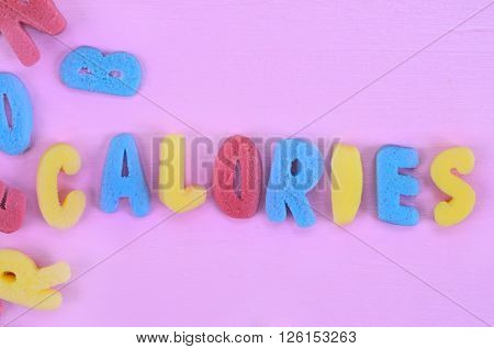 Colorful sugar Calories word on pink wooden table