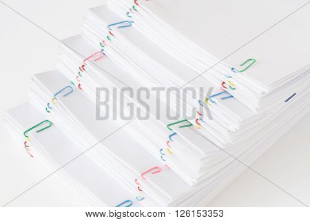 Colorful Paper Clip With Pile Of Overload Paperwork And Reports