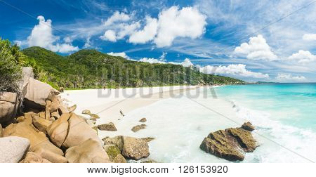 Beautiful and a famous beach Anse Petite seen from the granite boulders, La Digue island, Seychelles. Panorama