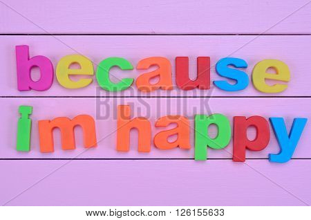 Words Because i'm happy on purple wooden table