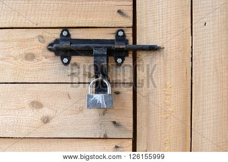 Padlock and latch on a wooden door