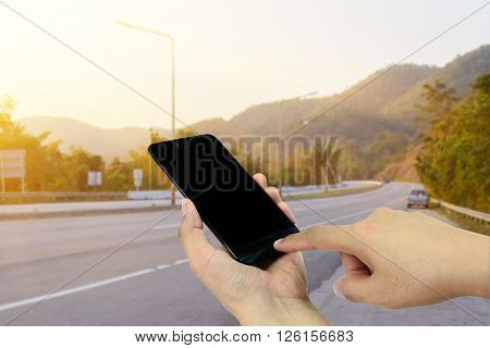 Hand holding and touch screen smart phone,cellphone on roadside with sunset Mountain landscapes in background Asian