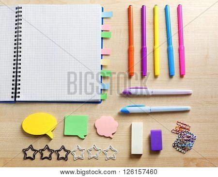 Notebook with bookmarks on wooden table