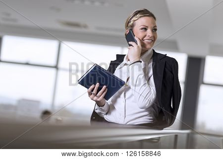 Modern business woman having a phone conversation with a colleague
