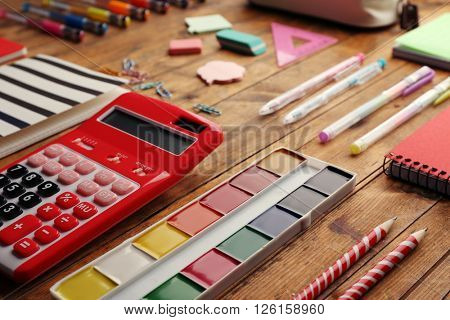 School set with paints, calculator, notebooks on wooden background