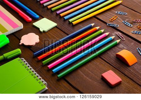 School set with notebooks, erasers and colored pencils on wooden background