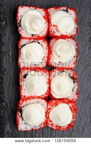Homemade sushi set with red tobiko and cream cheese on black plate overhead view