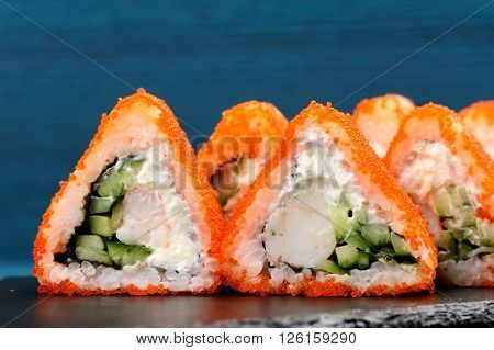 Tasty fusion rolls with orange tobiko roe cream cheese and cucumber on blue background closeup