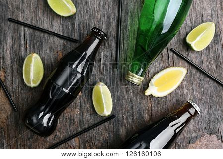 Fresh cocktail preparation: slices of citruses, straws and bottles on rustic table background, top view
