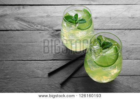Glasses of lemon soda with fresh mint on rustic wooden background