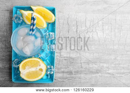 Fresh cocktail with lemon slices and ice on blue plate, top view