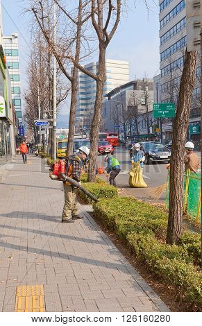 SEOUL SOUTH KOREA - MARCH 14 2016: Municipal workers gather fallen leaves on the street of Seoul Korea