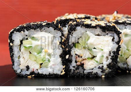 Homemade sushi rolls with black tobiko cucumber and cream cheese on red background closeup