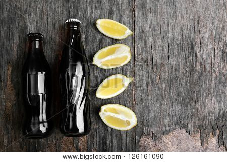 Soda bottles with lemon slices  on rustic wooden table