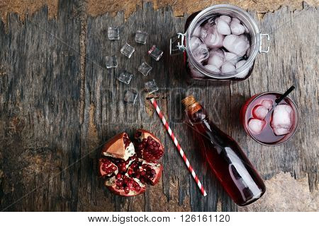 Fresh cocktail preparation: soda bottle, pomegranate, straws on rustic table background, top view