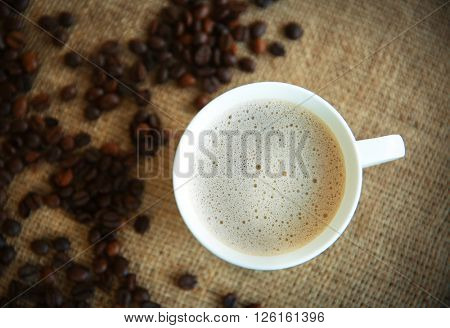 Cup of coffee with beans on sackcloth, top view
