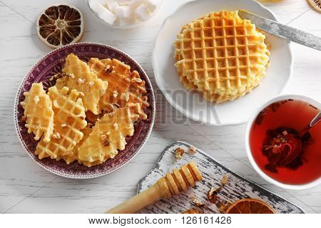 Fresh crumbled waffles on plate, top view