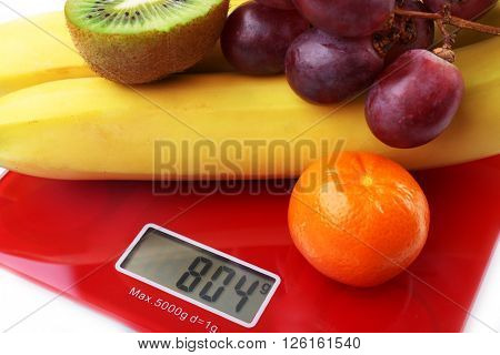 Fresh fruits on red digital kitchen scales, close up