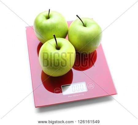 Three apples on digital kitchen scales, isolated on white
