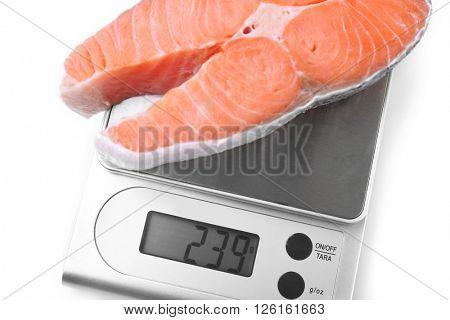 Row salmon steak on digital kitchen scales, isolated on white