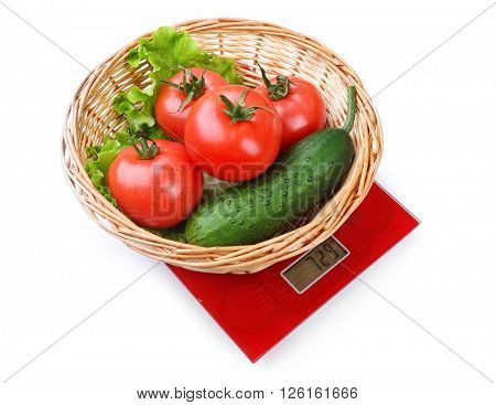 Basket with fresh vegetables on digital kitchen scales, isolated on white