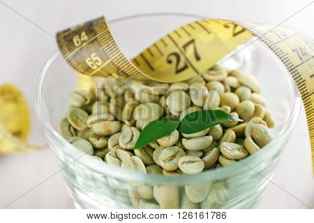 Green coffee beans in a cup with measuring tape, close up