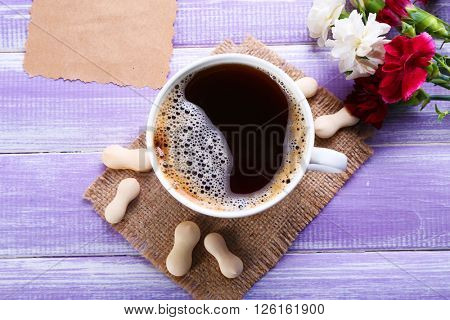 Cup of coffee with candies, flowers and and blank piece of paper on wooden background