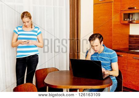 Couple at home, man working on laptop woman using mobilephone