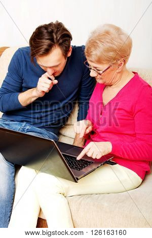 Mother and son sitting on the couch and watching something on laptop