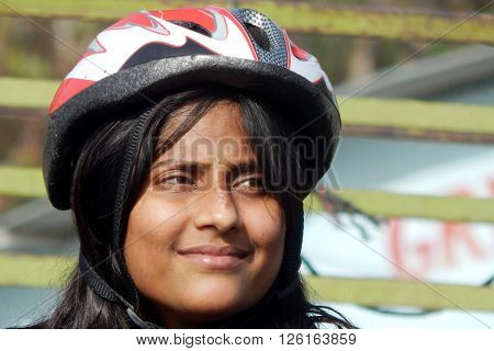 HYDERABAD,INDIA-MARCH 20:Portrait of Indian woman cyclist wearing safety helmet on a busy road on March 23,2016 in Hyderabad,India.