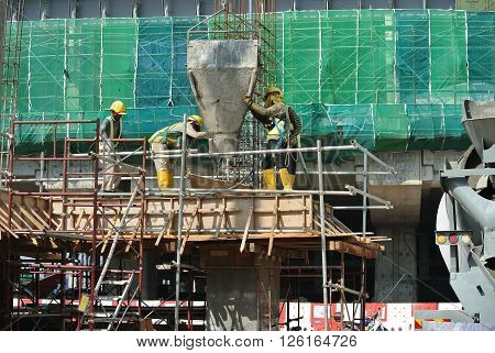SELANGOR, MALAYSIA -DECEMBER 12, 2015: A group of construction workers pouring wet concrete using concrete bucket into the timber form work at the construction site.