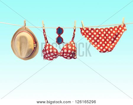 Beach outfit. Summer clothes and accessories stylish set. Fashion swimsuit bikini red polka dots, sunglasses, hat on rope. Essentials creative tropical look on blue. Ocean sea vacation concept, vintage