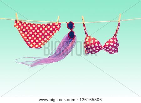 Beach outfit. Summer clothes and accessories stylish set. Fashion swimsuit bikini red polka dots, sunglasses on rope. Essentials creative tropical look on blue. Ocean sea vacation concept, vintage