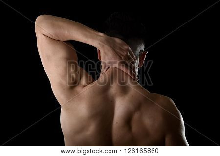 back of young muscular sport man holding sore neck with his hand and touching or massaging cervical area suffering body pain in spine back health problem isolated on black background