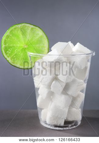 Plastic glass full of sugar with lime on grey background