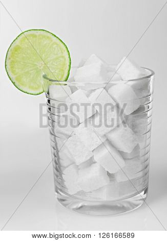 Old fashioned glass with lump sugar and slice of lime on grey background