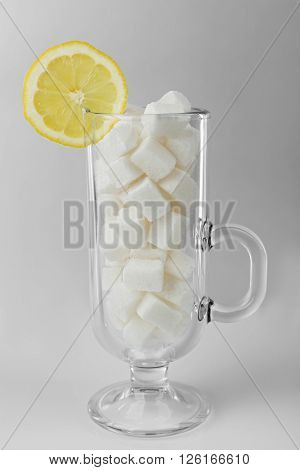 Irish coffee glass with lump sugar and slice of lemon on grey background